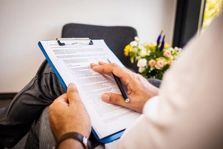 Therapeut mit Klemmbrett, Kugelschreiber und Manual